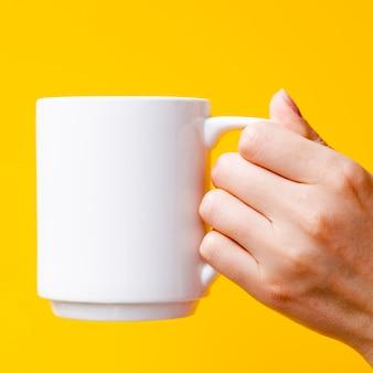 マグカップと黄色の背景を持つクローズアップ人