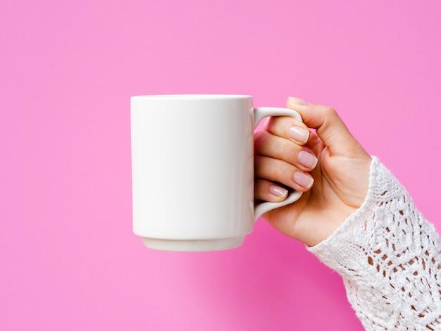 マグカップとピンクの背景を持つクローズアップ女性