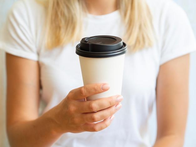 コーヒーカップを持つクローズアップ女性