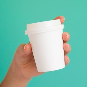 白いコーヒーカップを保持しているクローズアップの女性