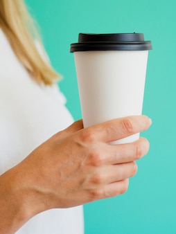 Крупным планом женщина с чашкой кофе и зеленым фоном