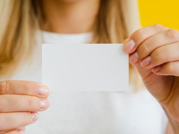 ビジネスカードを保持しているクローズアップの女性