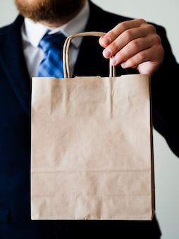 Крупным планом элегантный мужчина с бумажной сумкой