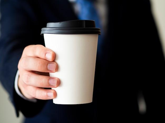 Макро рука держит чашку кофе макет