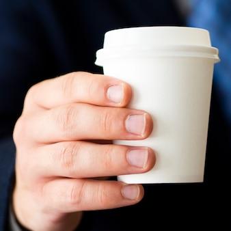 Рука крупным планом держит маленький макет кофейной чашки