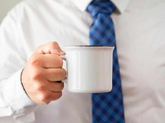 Рука крупным планом держит макет кружка кофе