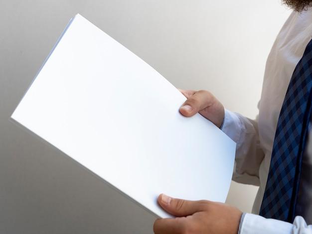 紙のモックアップのスタックを保持している手