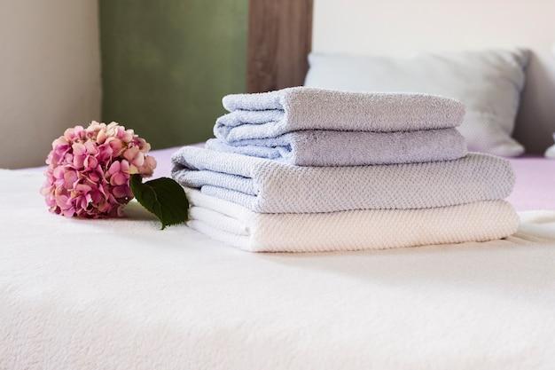 ピンクの花とベッドの上のタオルの配置