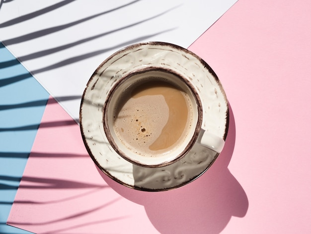 Плоская лежал чашка кофе на розовом фоне