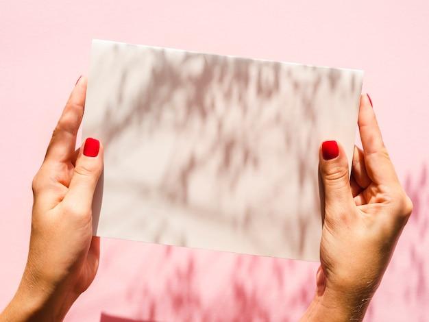 Макро руки держат белую бумагу