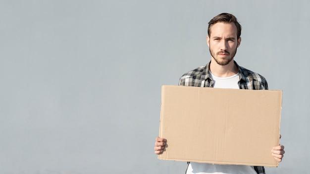 Молодой человек держит доску с макетом