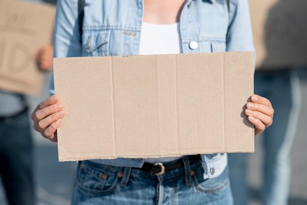 Макро протестующий держит доску с макетом