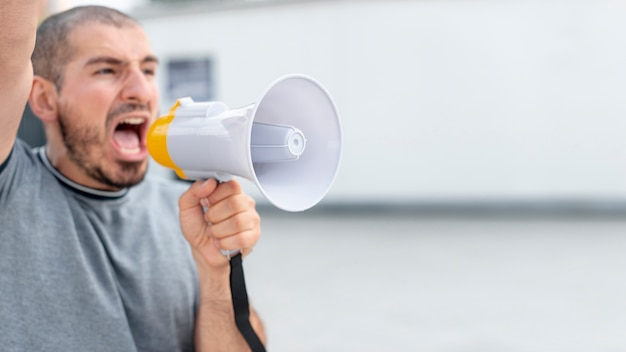 Протестующий спереди кричит с мегафоном