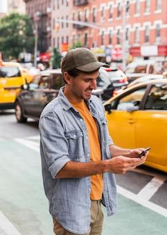 携帯を見てキャップを持つ男