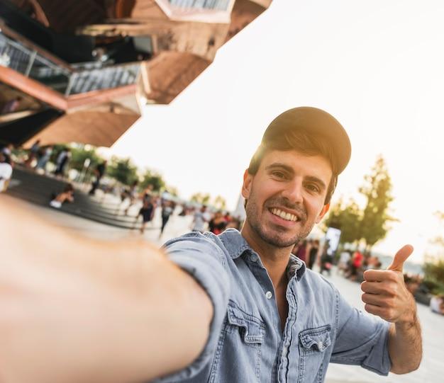 若い男がカメラに笑顔を身振りで示す