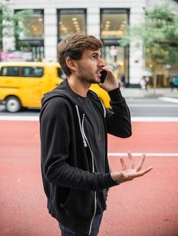 若い男がスマートフォンで話しながら身振りで示す
