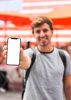 若い男がスマートフォンの画面を表示
