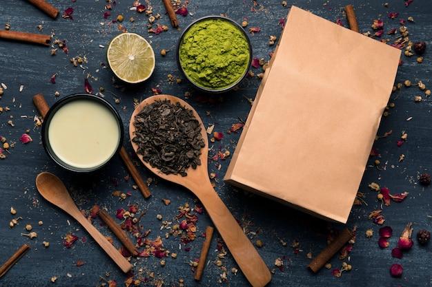 Бумажный пакет с макетом рядом с ингредиентами азиатского чая маття