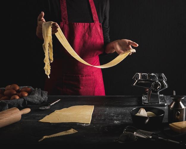 Крупным планом человек с красным фартуком, держа тесто