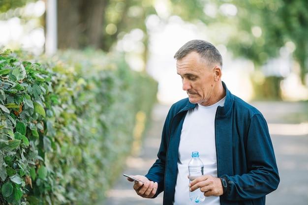 年配の男性が携帯電話を見て屋外