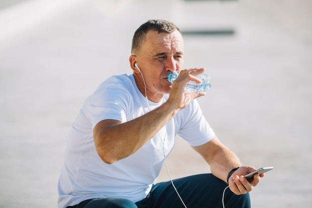 Мужчина пьет воду с наушниками в ушах