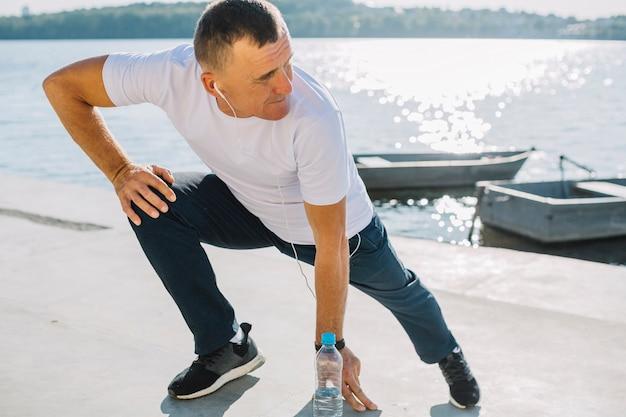 湖の近くのスポーツの練習の男