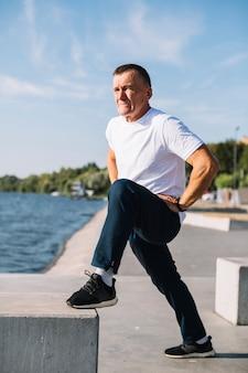 Мужчина поднимает ногу у озера