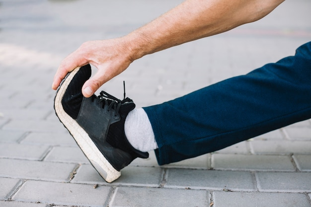 Спортивный мужчина вытянул ногу на аллее