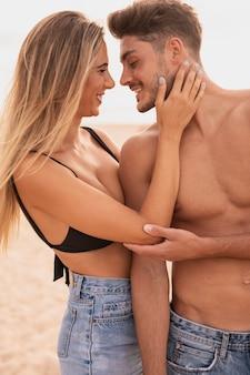ビーチでスマイリーと若いカップル