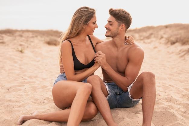 お互いを見てビーチで若いカップル