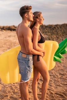 夕日を見てビーチで若いカップル