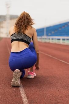 陽気な女性は彼女の靴ひもをバインドします