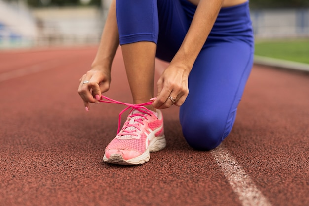 Бегун женщина связывает обувь шнурками