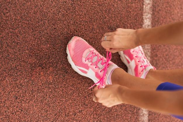 トップビュー陽気な女性は靴ひもをバインドします