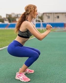 練習前に準備運動をする陽気な女性