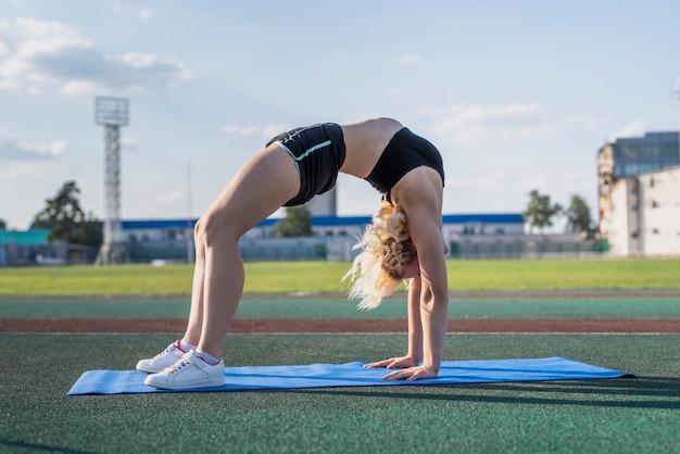 Спортивная женщина в позе моста на коврике