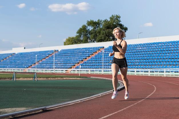 Тренировка бегущей женщины на стадионе