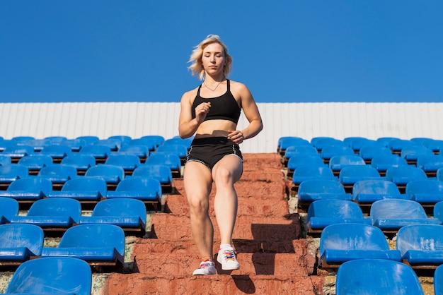 低角度の陽気な女性の階段運動