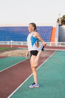 マラソン前にウォーミングアップの若いランナー