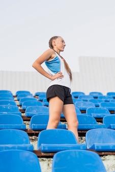 スタジアムで低角度の陽気な女性