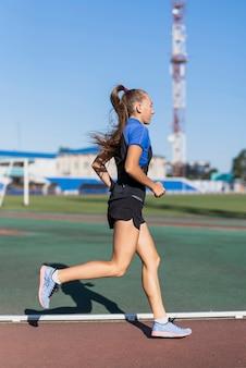 Молодая женщина бегун на стадионе