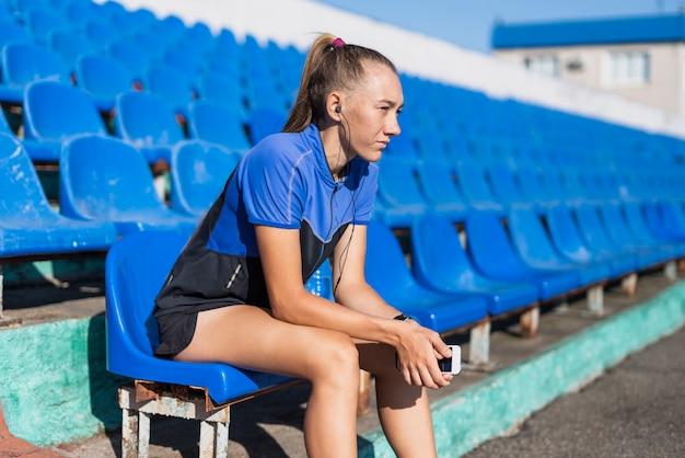 スタジアムに座っている陽気な女性