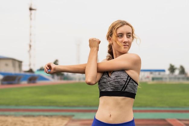マラソン前にストレッチランナーの若い女性