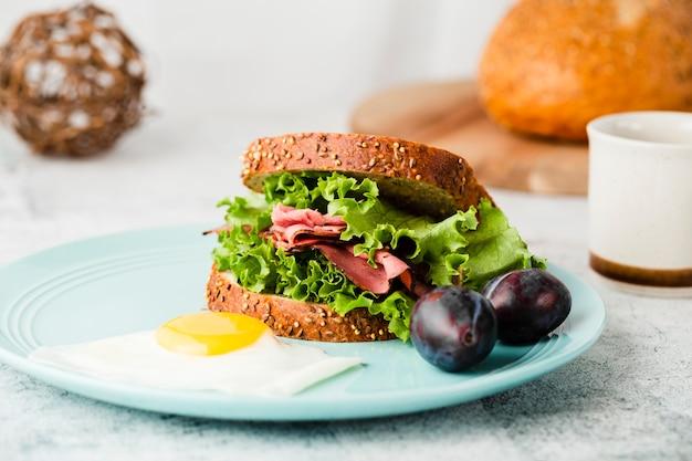 Взгляд конца-вверх вкусного сандвича рядом с сливами