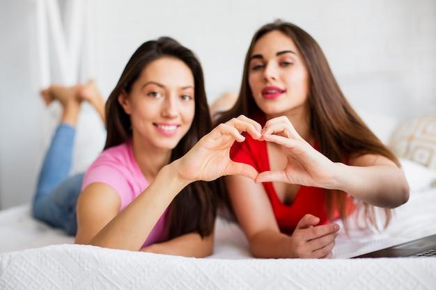 Молодые женщины, делающие сердечко руками