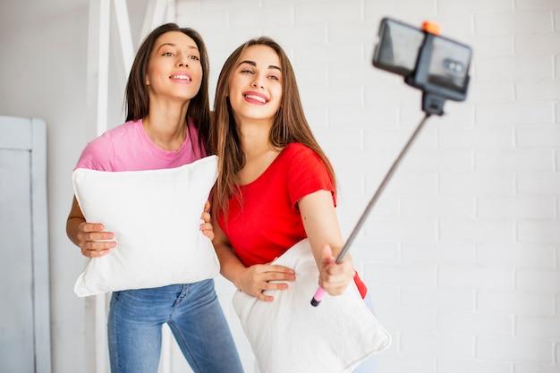 写真を撮る枕を持つ若い女性
