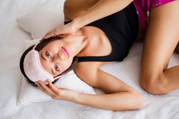 睡眠マスクで遊ぶ高角の女性
