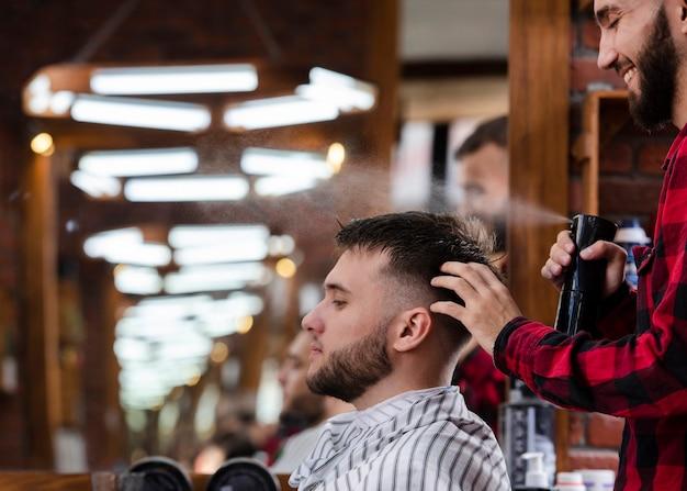 クライアントの髪をスプレーする美容師