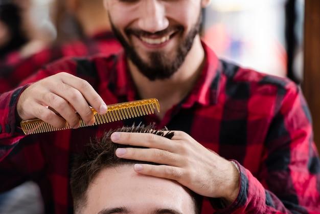 Парикмахер измеряет волосы перед стрижкой