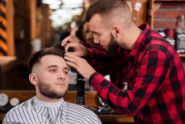 Парикмахер, заботящийся о волосах клиентов